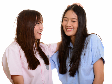 Two young happy Asian teenage girls smiling and patting her frie