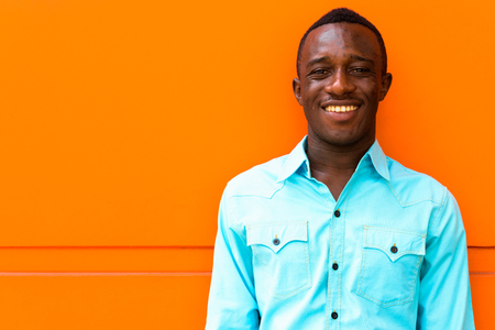 Young happy black African man smiling while leaning against oran