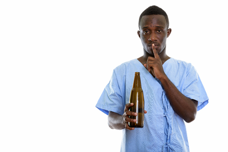 Studio shot of young black African man patient holding bottle of