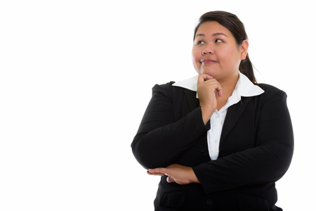 Studio shot of young fat Asian businesswoman thinking while look
