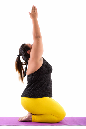 Studio shot of young fat Asian woman sitting while doing yoga po