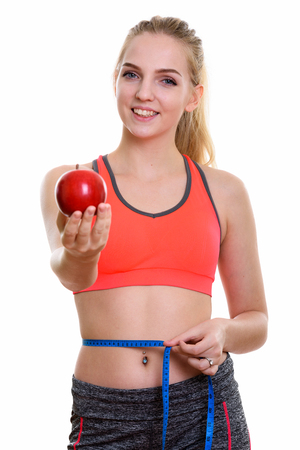 Young happy teenage girl smiling while giving red apple and meas Stock Photo