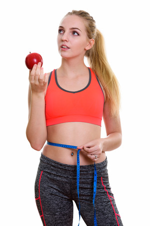 d44d4f2bdeb6e Young beautiful teenage girl holding red apple while thinking an Stock Photo