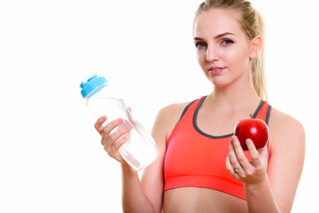 Studio shot of young beautiful teenage girl holding water bottle