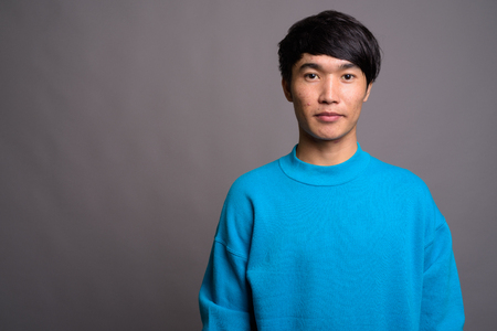 Young Asian man wearing blue sweater against gray background