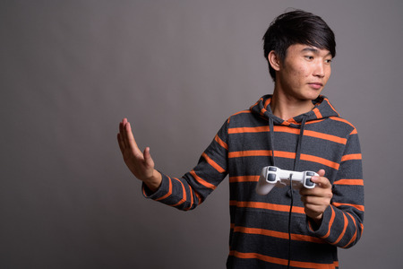 Young Asian man playing games against gray background