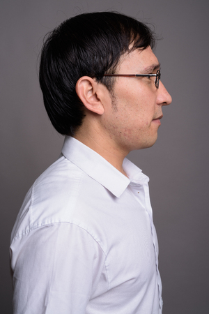Young Asian nerd man wearing eyeglasses against gray background