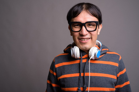 Young Asian nerd man wearing hoodie and headphones against gray Standard-Bild