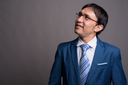 Portrait of young Asian businessman against gray background Standard-Bild