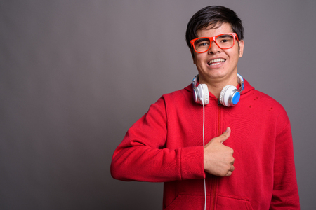 Young Asian teenage boy wearing headphones against gray backgrou Standard-Bild