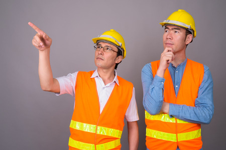 Two young Asian men construction worker together against gray ba
