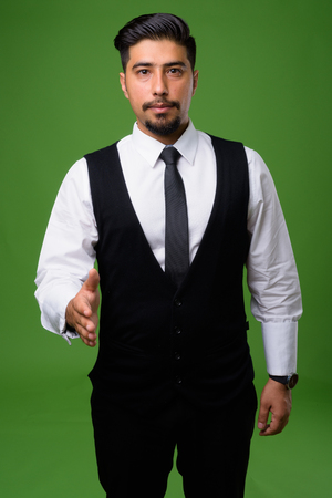 Young bearded Iranian businessman against green background