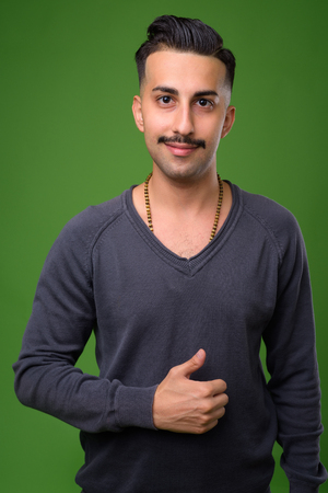 Young handsome Iranian man with mustache against green backgroun