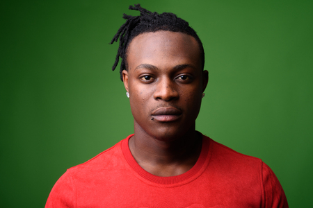 Young handsome African man from Kenya against green background Stock Photo