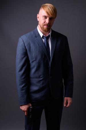 Bearded businessman with handgun against gray background