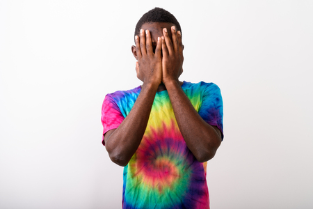 Studio shot of young black African man covering his face with bo