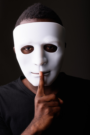 Studio shot of young black African man in dark room wearing mask