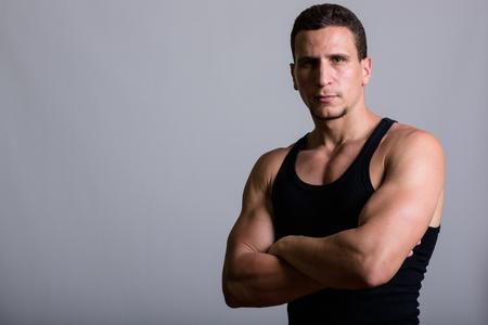 Studio shot of young muscular Persian man wearing sleeveless wit