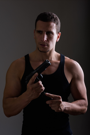 Studio shot of young muscular Persian man reloading gun while th