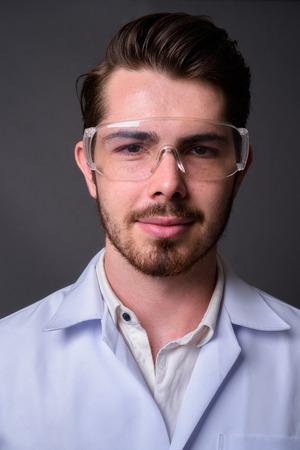 Jeune bel homme barbu médecin portant des lunettes de protection aga