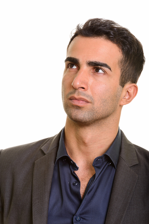Portrait of young handsome Persian businessman thinking