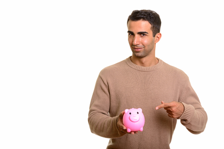 Portrait of young handsome Persian man with piggy bank