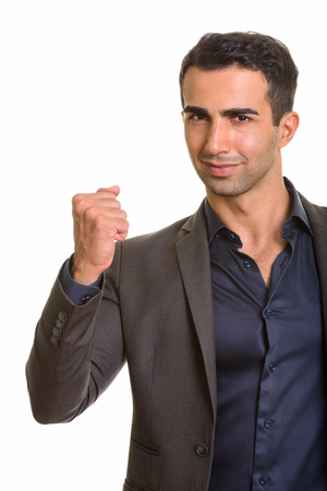 Portrait of young handsome Persian businessman with arm raised