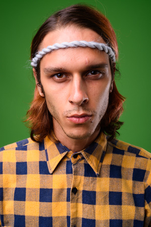 Studio shot of rebellious young man against green background