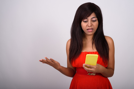 Studio shot of young Persian woman using mobile phone while look