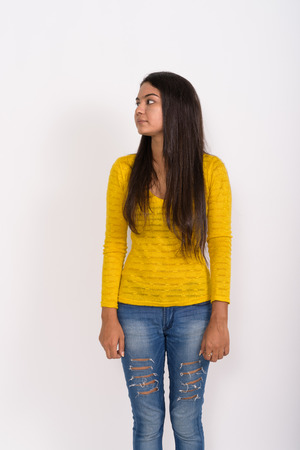 Profile view of young Indian woman standing while thinking with