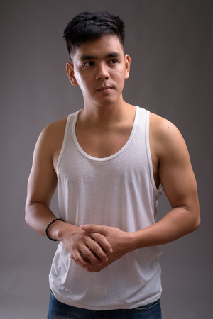 Young handsome Asian man wearing tank top against gray backgroun Stock Photo