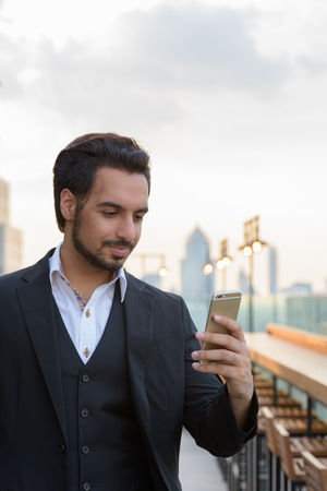 Young handsome Indian businessman using mobile phone at rooftop 版權商用圖片