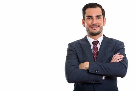 Studio shot of happy young handsome businessman smiling with arm