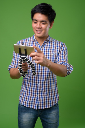 Young handsome Filipino man against green background 版權商用圖片