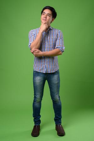 Young handsome Filipino man against green background Standard-Bild
