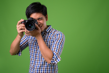 Young handsome Filipino man against green background Zdjęcie Seryjne
