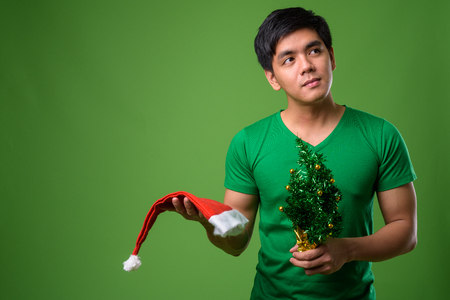 Young handsome Filipino man ready for Christmas against green ba
