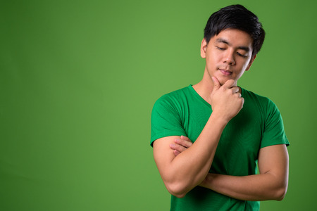 Young handsome Filipino man against green background 免版税图像