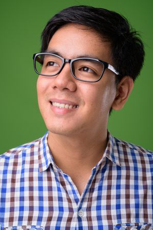 Young handsome Filipino man against green background Stock fotó