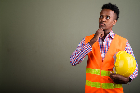 Young handsome African man construction worker against colored b
