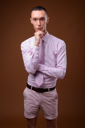 Young handsome androgynous businessman against brown background