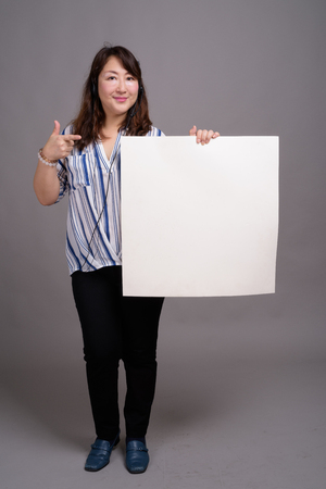 Full length portrait of Japanese businesswoman holding white board