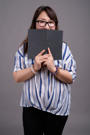 Asian businesswoman holding book against gray background Фото со стока