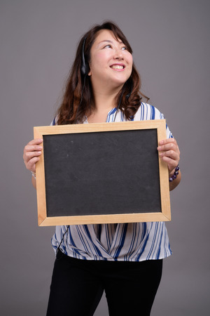 Mature Asian businesswoman holding blackboard with copy space