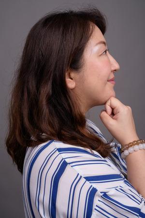 Profile view of mature beautiful Asian businesswoman thinking Imagens