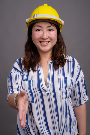 Mature Asian businesswoman construction worker wearing hardhat 写真素材