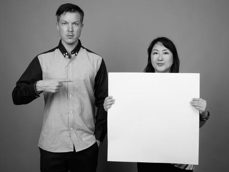 Portrait of multi ethnic diverse couple in studio showing copy space