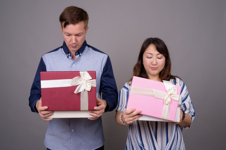 Businessman and mature Asian businesswoman holding gift box