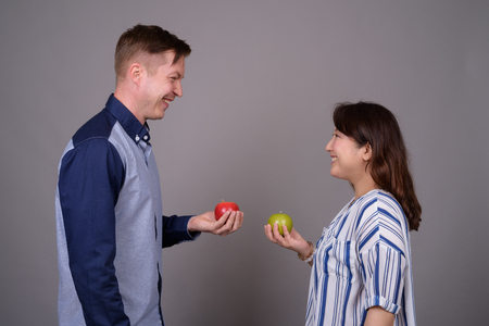 Multi ethnic diverse couple in studio holding green and red apple fruit