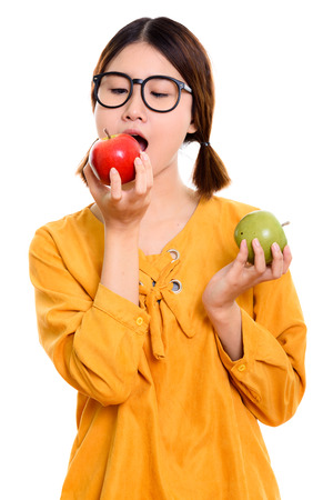 Young beautiful Asian woman eating red apple while holding green Banco de Imagens
